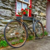 Rusty bike leaning against a stone cottage wall.