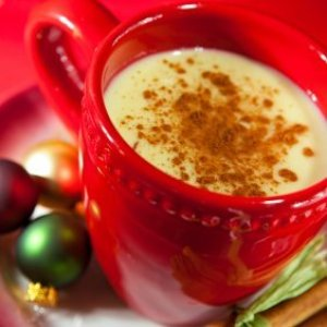 Eggnog Recipes, Eggnog in a festive red cup with small ornaments on the saucer.