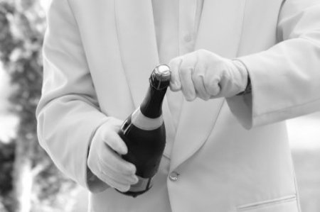 Man in White Gloves and Suit Opening a Bottle of Champagne