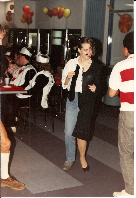A halloween costume where the right side is a man in a white shirt, jeans and a tie, and the left is a woman in a black dress with heels.