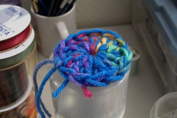 Crochet pin cushion on spray paint can lid, closeup.