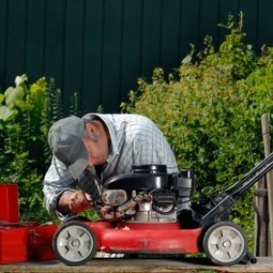 A man winterizing his lawnmower.