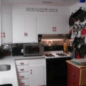 Pots, pans and lidshanging on the pegboard in kitchen.