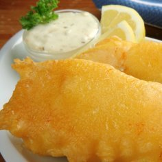 A plate of fried fish with tartar sauce and lemon wedges.