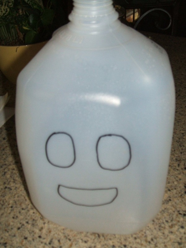 White one gallon milk jug with two round eyes and a mouth drawn on.