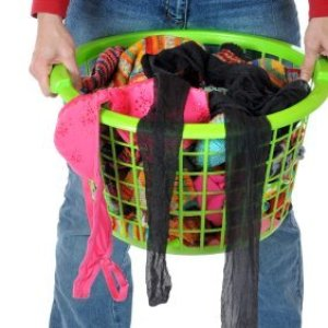 Woman carrying a laundry basket full of socks.