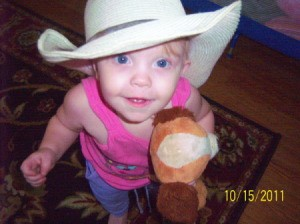 A toddler with a cowboy hat and a toy hobby horse.