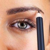 A woman using an eyebrow pencil.