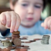 A young child counting coins.