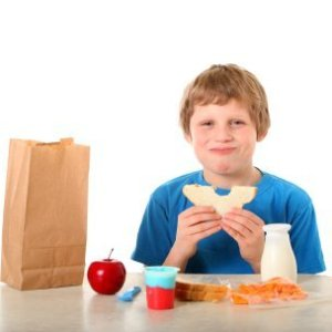 A child eating a brown bag lunch.
