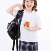 Young Girl with Backpack and Apple Ready for School