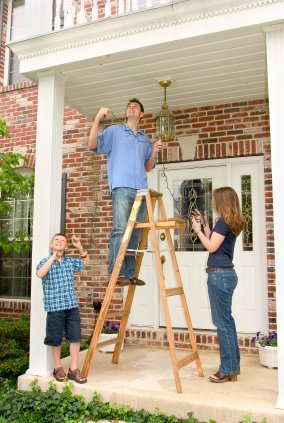 Family Working on Hanging Outdoor Christmas Lights