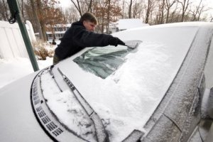 Keeping Your Windshield Free of Snow and Ice, Man Cleaning Snow and Ice off of Windshield