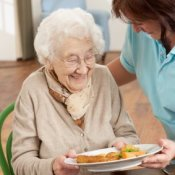 An elderly woman being served a meal.