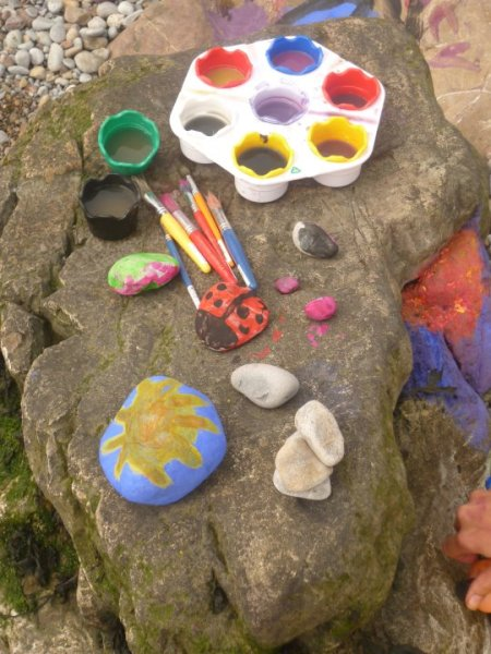 Paints and Paintbrushes Sitting on Large Rock