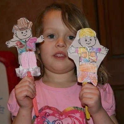 A girl holding two paper dolls.