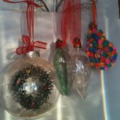 Three clear Christmas ornaments with decorative inclusions.