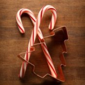 Two crossed candy canes and a tree shaped cookie cutter.
