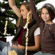 Kids making popcorn garland.