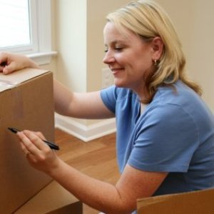 Tips for Organizing Your Move, A woman labeling moving boxes.