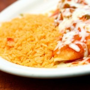 Plate of Spanish rice with enchiladas.