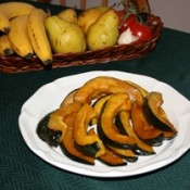 Sweet acorn squash displayed on white plate in front of fruit basket.