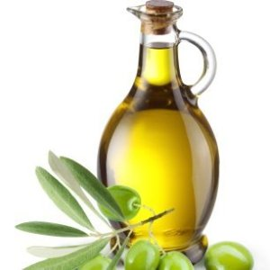 Bottle of olive oil with olives and leaves in the foreground.