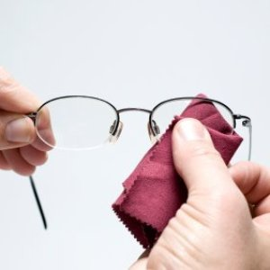 Cleaning eyeglasses with a cloth.