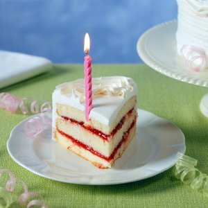 A slice of birthday cake with a half candle.