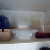 Shelf with plastic containers stored with lids.