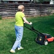 Lady pushing a lawn mower.