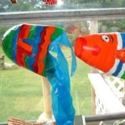Two pop bottle fish hanging in a window.