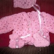Pink crochet baby sweater.