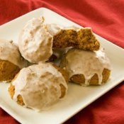 A plate of iced pumpkin cookies made from a pumpkin cookies recipes.