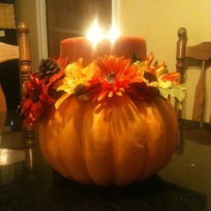 Styrofoam pumpkin centerpiece with candle lit.