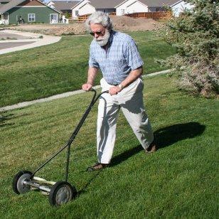 Environmentally Friendly Lawn Mowers. A man pushing a reel mower.