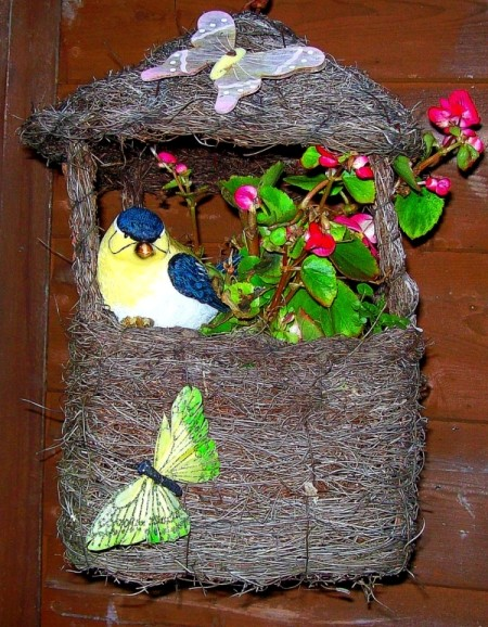 A garden decoration with a blooming plant, artificial butterflies and a bird.