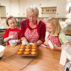 Grandmother showing her granddaughters how to make muffins.