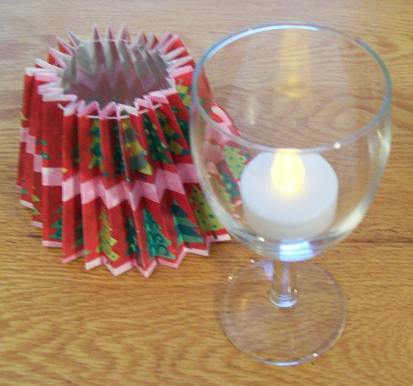 Glass with tea light inside and shade next to in on table.