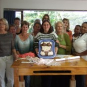 Ladies sewing group with a torso cake in bra and panties.