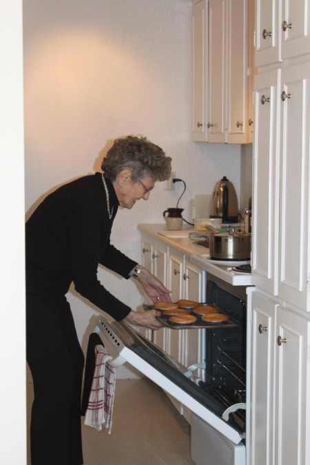 Author's mother removing baked goods from the oven.