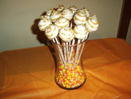 Cake pops in a jar of candy corn.