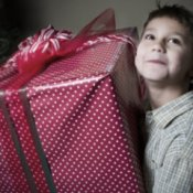 A boy holding a large wrapped Christmas present.