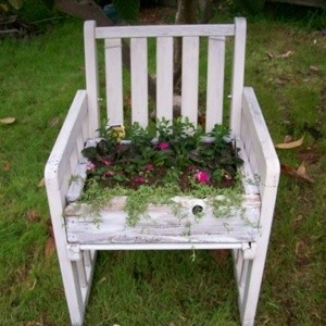 White chair turned into a planter with flowers in it.