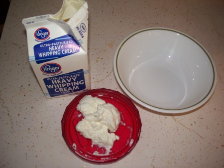 Carton of heavy whipping cream, 2-3 tablespoons of yogurt in red bowl, and a white bowl