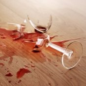 Removing Red Wine Stains from Hardwood Floors, Broken glass of red wine on wood floor.