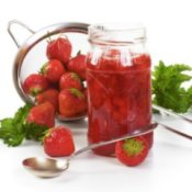 Fresh strawberries in a jar with a colander in the background.