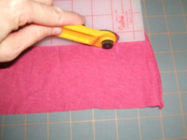 Rotary knife cutting pink jersey fabric