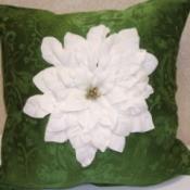 White Poinsettia on Green Pillow