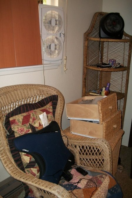 A wicker chair and shelf in the newly organized bedroom.